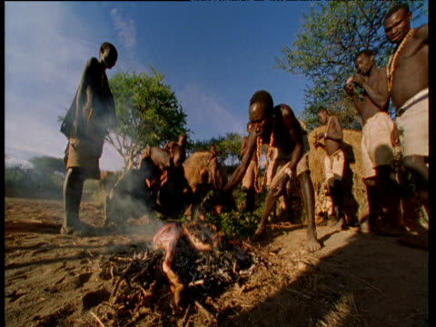 Hadzabe tribe cook meat on campfire