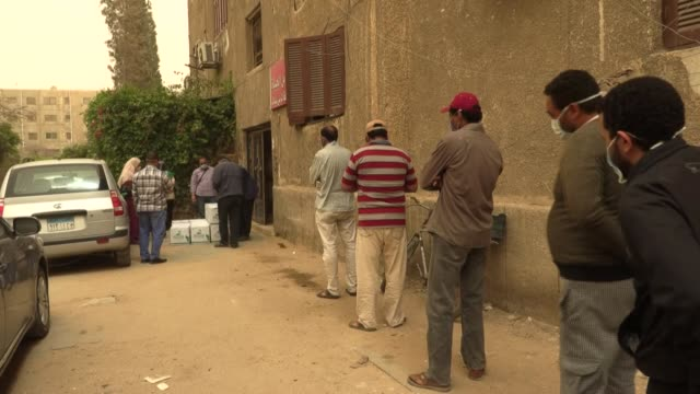 haggard and dishevelled from the stress of making ends meet day labourers line up in cairo for food parcels after losing their jobs to the sharp... - egypt stock videos & royalty-free footage