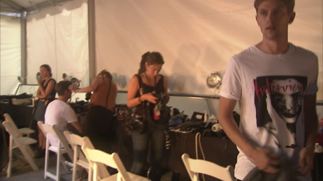 ms hair and makeup model getting his hair done ms tommy hilfiger walking backstage ms tommy hilfiger taking photos with ryan phillippe and james... - tommy hilfiger designer label stock videos and b-roll footage