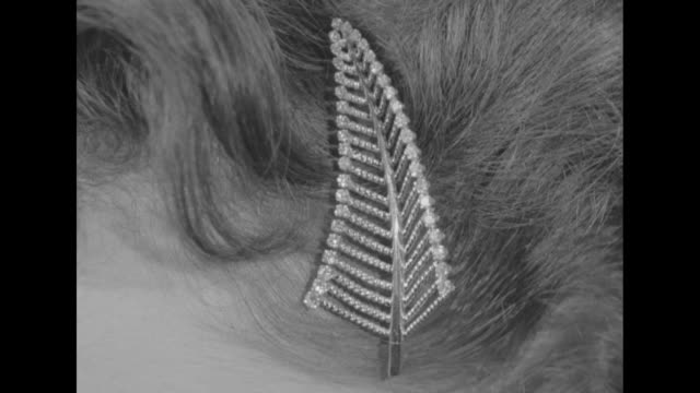 hair clip modeled after fern leaf / woman displays earrings and hair clip modeled after fern leaves / woman displays diamond pin resting on her chest... - hair accessory stock videos & royalty-free footage