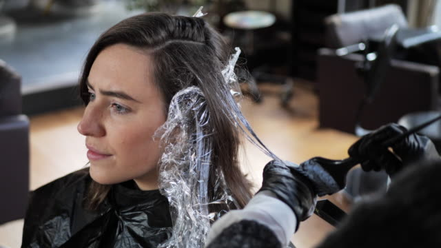 hair dresser and young woman dying her hair - film stock videos & royalty-free footage