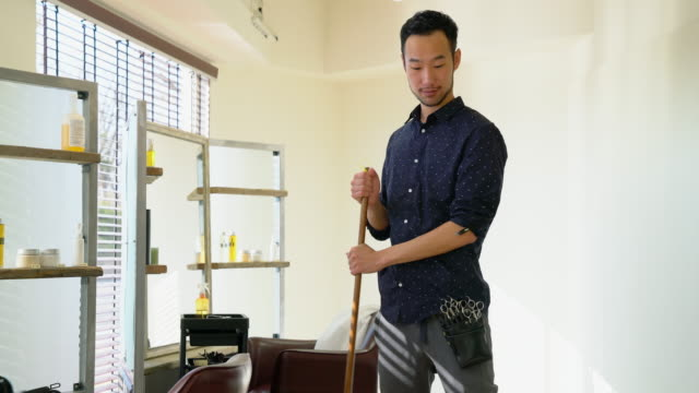 hair dresser sweeping up in his salon - beauty salon stock videos and b-roll footage