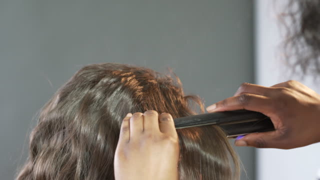 vidéos et rushes de a hair stylist using straightening irons to add a subtle wave to a models hair - hair straighteners
