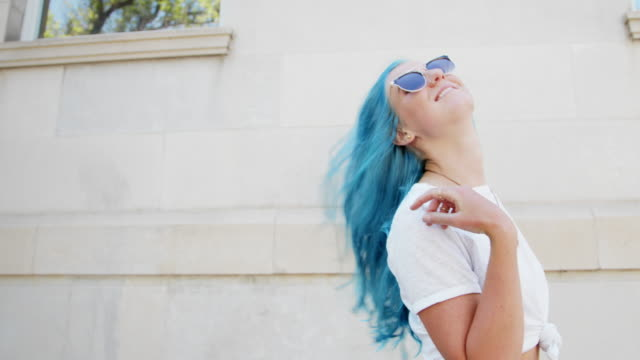 hair toss shot of a unique, spunky, fashionable, joyful, happy young woman with fun cute teal blue green dyed hair standing outdoors in the summer - hair toss stock videos & royalty-free footage
