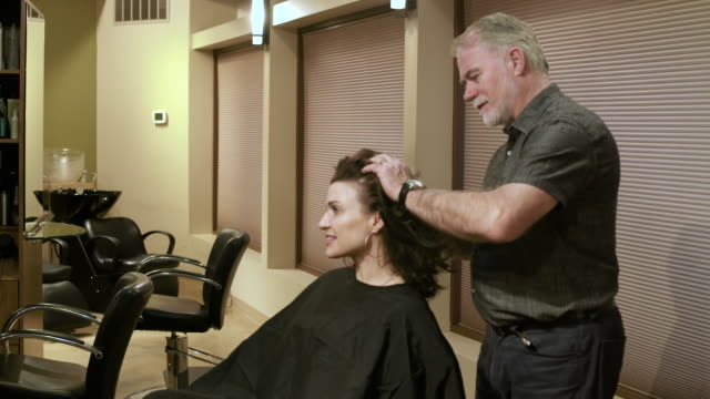 hairdresser adjusting hair of a mid adult woman - hoop earring stock videos and b-roll footage