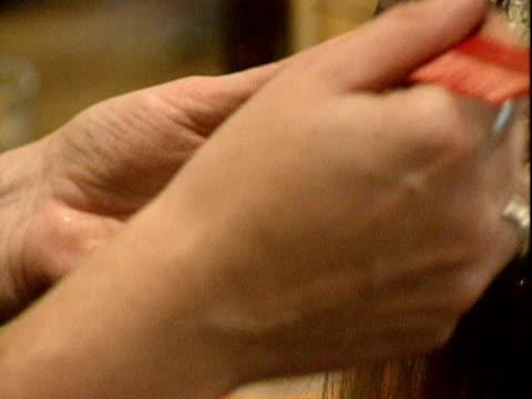 hairdresser applies dye to a customer's hair in a salon; 2000 - アルミホイル点の映像素材/bロール