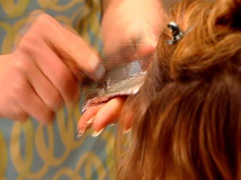 CU, Hairdresser applying cream dye on woman's hair
