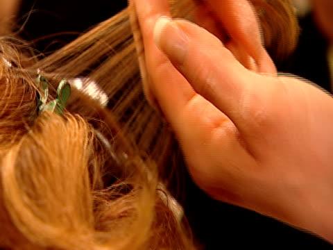 ECU, Hairdresser applying cream dye on woman's hair
