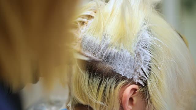 ブロンドの髪に髪の染料を適用する美容師 - ヘアケア点の映像素材/bロール