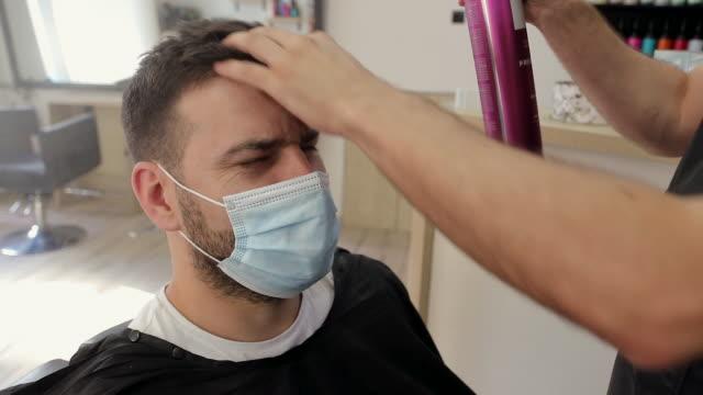 hairdresser applying hair spray on man's hair at hair salon - hair spray stock videos & royalty-free footage