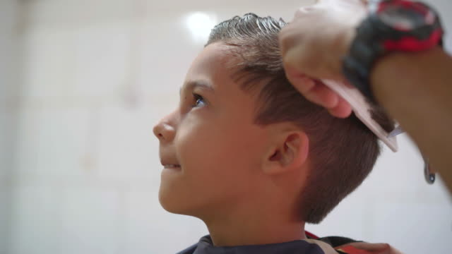 hairdresser cutting boy's hair with scissors - electric razor stock videos and b-roll footage