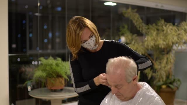vidéos et rushes de coiffeur faisant la coupe de cheveux à la maison dans l'homme aîné - coiffure