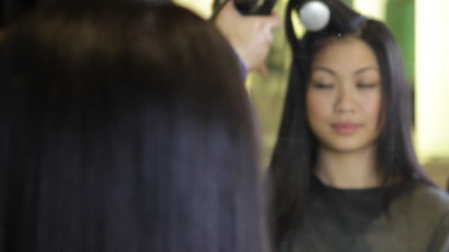 CU, R/F Hairdresser drying and brushing hair of female in hair salon
