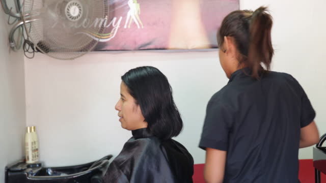 hairdresser is cutting the hair of a woman at a hair salon in piura peru - annuncio economico video stock e b–roll