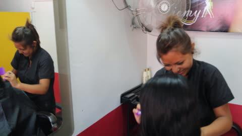 stockvideo's en b-roll-footage met hairdresser is cutting the hair of a woman at a hair salon in piura, peru. - rubriekadvertentie