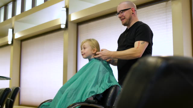 Hairdresser putting a cape on a girl