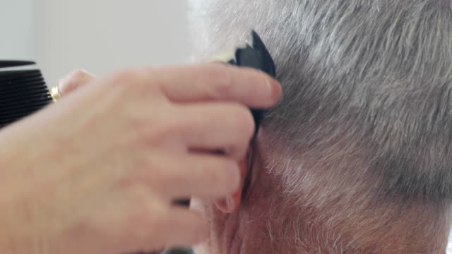 hairdresser shaving senior man behind ears with electric razor - electric razor stock videos and b-roll footage