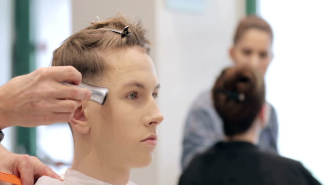 hairdresser shaving young man's head with small electric razor - electric razor stock videos and b-roll footage