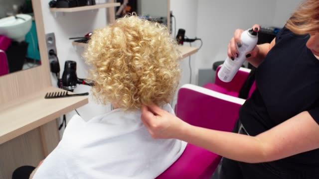 vidéos et rushes de laque spray coiffure sur des cheveux du client - cheveux frisés