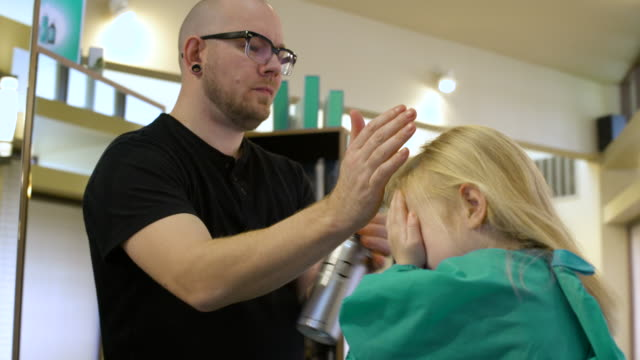 Hairdresser spraying hair of a girl