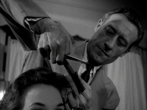 A hairdresser styles and cuts a woman's hair while a beauty therapist massages her hands in a beauty salon 1955