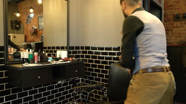 hairdresser turning and leaning on barber chair - barber chair stock videos & royalty-free footage