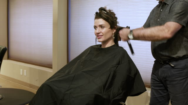 hairdresser using a curling iron on hair of a mid adult woman - hoop earring stock videos and b-roll footage