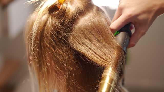 vídeos de stock, filmes e b-roll de cabeleireiro usando um enrolador de cabelo de ferro para fazer um estilo de cabelo ondulado moderno - cabelo encaracolado