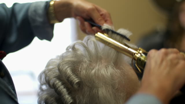 hairdresser using curling iron on elderly woman's hair - hairdresser stock videos & royalty-free footage