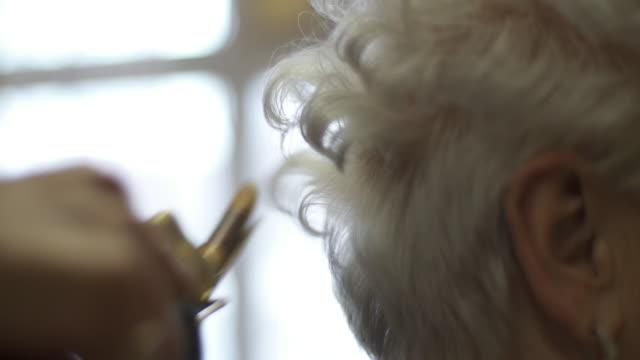 vídeos de stock e filmes b-roll de hairdresser using curling iron on elderly woman's hair - salão de beleza