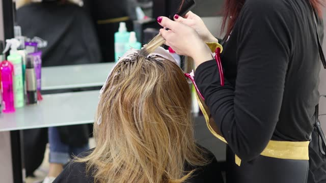 hairdresser using foils to color highlights on customer's hair - highlights hair stock videos & royalty-free footage