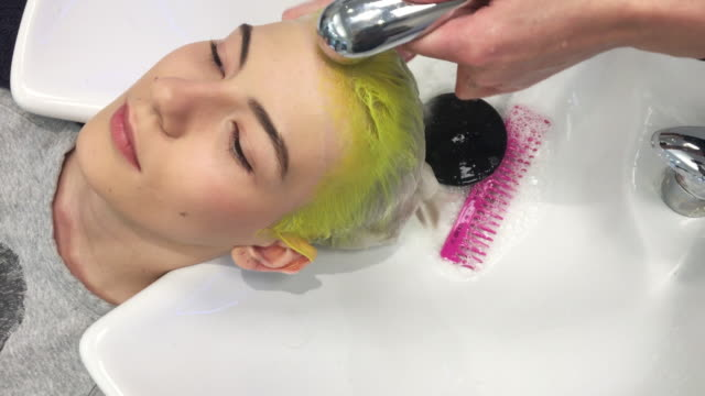 hairdresser washing dyed hair of a young woman - washing hair stock videos & royalty-free footage
