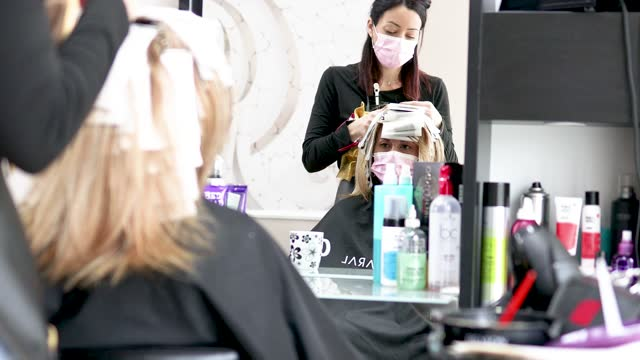 hairdresser with protective mask making highlights to a customer and using foils when doing so - caucasian ethnicity stock videos & royalty-free footage