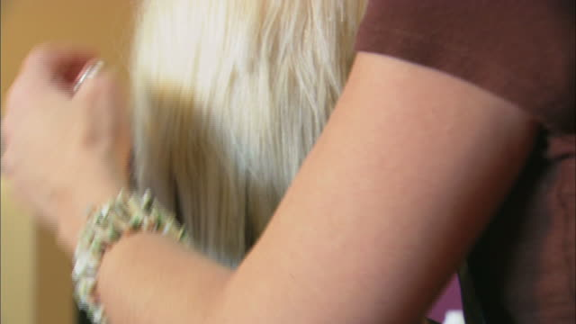hairdresser working on platinum blond woman's hair - platinum stock-videos und b-roll-filmmaterial