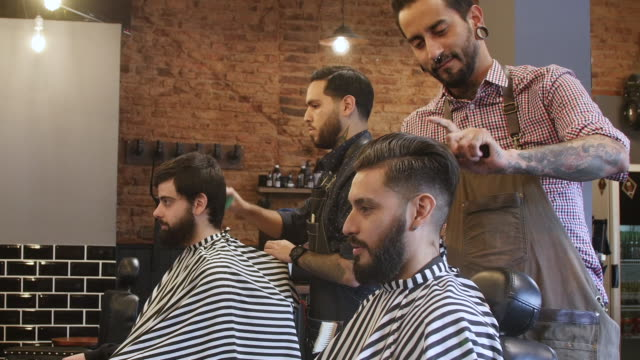 hairdressers cutting hair of clients in salon - stile di capelli video stock e b–roll