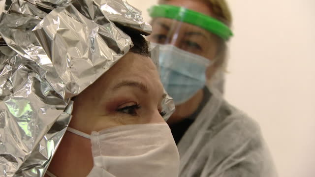 """hairdressers reopens in milan italy after some coronavirus lockdown restrictions are lifted ppe is worn - """"bbc news"""" video stock e b–roll"""