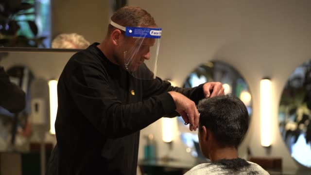 hairdressers wear a face shield as they cut clients hair at hershesons hair salon on july 7, 2020 in london, england. a appointments have been... - hairstyle stock videos & royalty-free footage