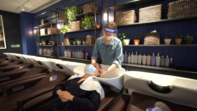 hairdressers wear a face shield as they cut clients hair at hershesons hair salon on july 7 2020 in london england a appointments have been extended... - beauty salon stock videos & royalty-free footage