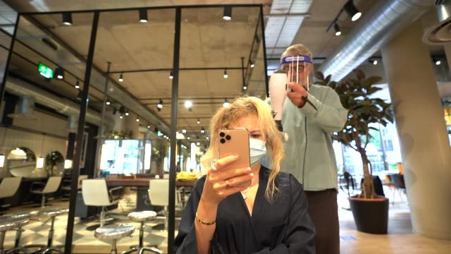 hairdressers wear a face shield as they cut clients hair at hershesons hair salon on july 7 2020 in london england a appointments have been extended... - hairdresser stock videos & royalty-free footage