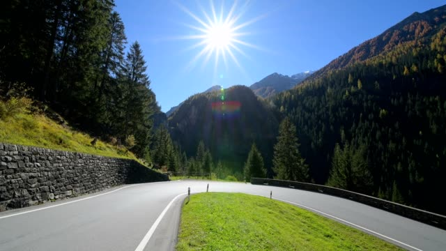 hairpin turn on pass road with sun, bergün, grisons, switzerland, european alps - empty road stock videos and b-roll footage