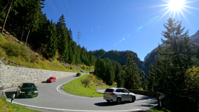 hairpin turn on pass road with traffic and sun, bergün, grisons, switzerland, european alps - bergstrecke stock-videos und b-roll-filmmaterial