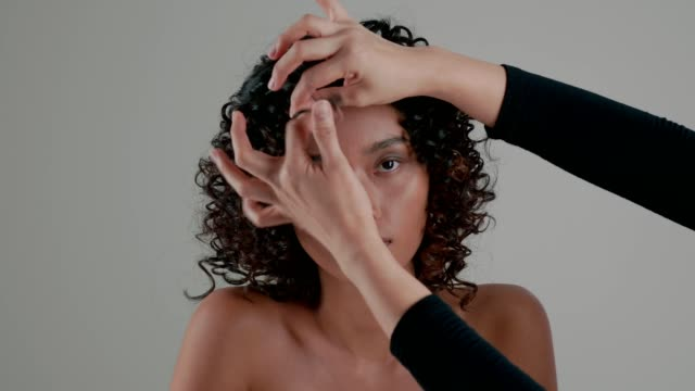 Hairstyle: hair stylish working with model for doing art of wavy hair