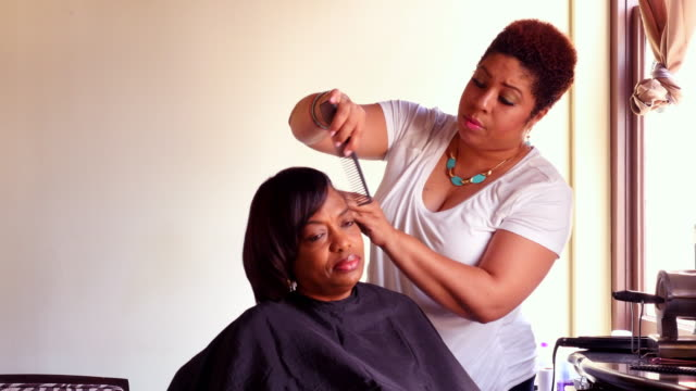 ms hairstylist straightening clients hair in salon - adjusting stock videos & royalty-free footage