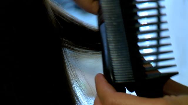 Hairstylist straightening some hair