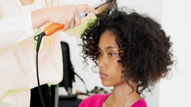 hairstylist using a curling iron to firm ringlets, closeup view of the hand.beautiful woman getting haircut by hairdresser in the beauty salon.black ethnicity - hairdresser stock videos & royalty-free footage