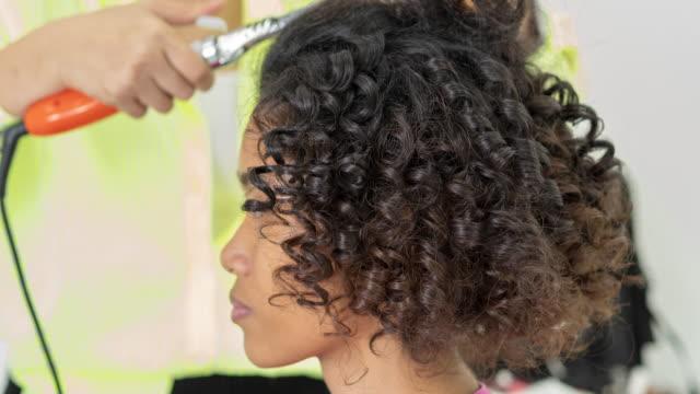 vidéos et rushes de coiffeur à l'aide d'un fer à friser à boucles fermes, vue de la main. belle femme se coupe de cheveux en salon de coiffure à l'ethnicité de salon.black de beauté - cheveux frisés
