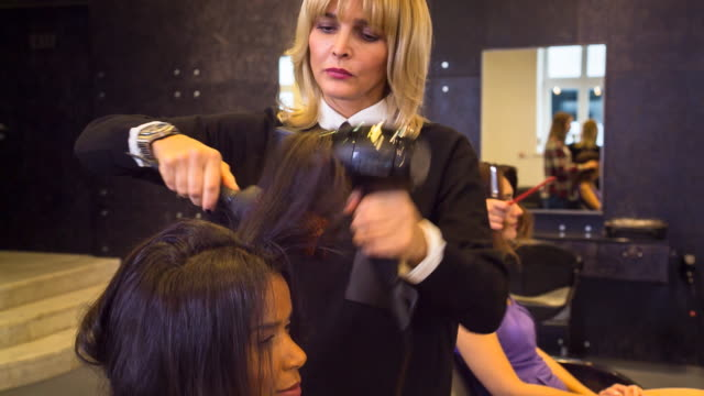 cu hairstylists blowdrying customer´s hair in salon - hairdresser stock videos & royalty-free footage