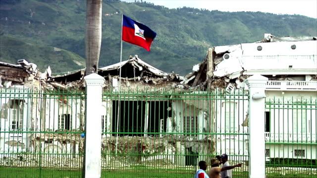 stockvideo's en b-roll-footage met haitian flag flying over the ruined presidential palace - haïti