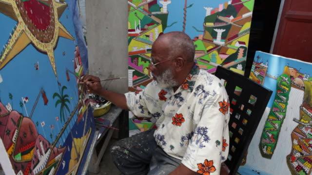 stockvideo's en b-roll-footage met haitian octogenarian artist prefete duffaut works on one of his post earthquake paintings. - haïti