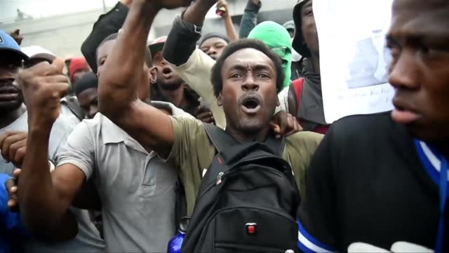 haitian protesters chant down with the americans long live putin after burning an american flag in the haitian capital portauprince on the ninth day... - flag haiti stock videos & royalty-free footage